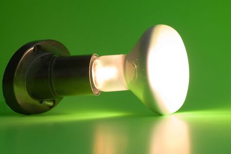 threaded: Glowing light bulb on a green background