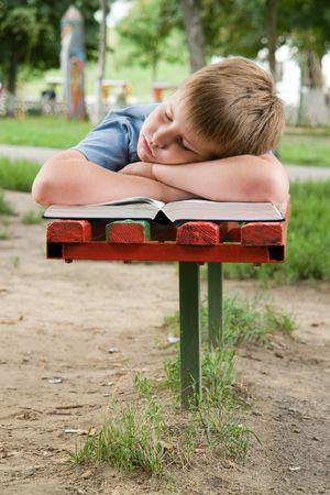 schoolboy sleeps on a bench in park photo