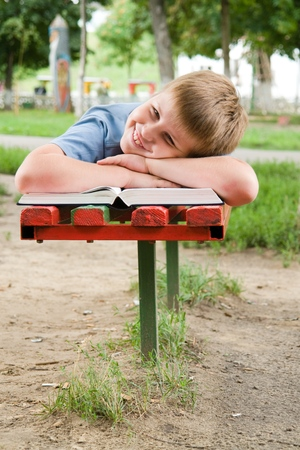 schoolboy reads the book on a bench in park photo