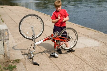 tighten: little boy repairs the bicycle on quay