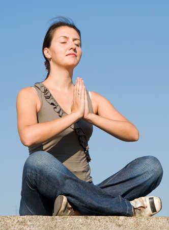 meditates: Meditation. The girl meditates with sky at background.