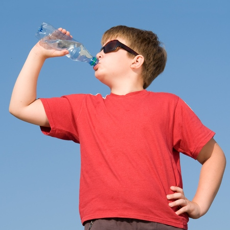 boy drinks water on a blue sky