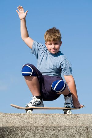 boy with skateboard on a blue sky