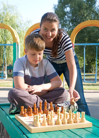 Mum and the son play a chess in park