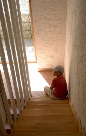 sad little boy sits at ladder steps photo
