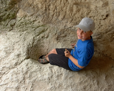 eyes cave: little boy in an ancient mountain cave