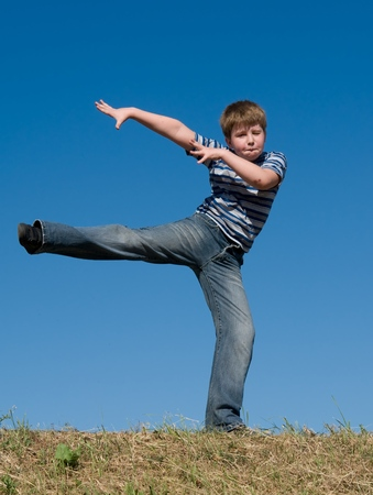 The dancing little boy against the blue sky Stock Photo