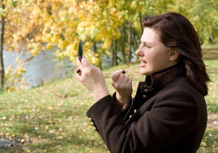 Autumn. Beautiful young woman put on lipstick. photo