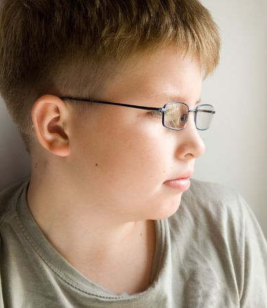 little serious boy in glasses near a window