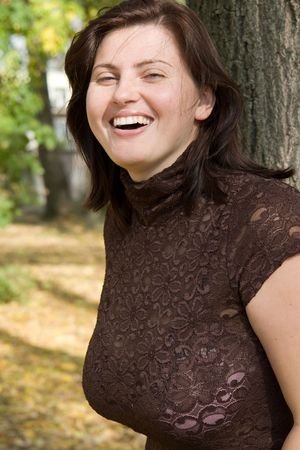 Smiling beautiful woman near a tree in autumn park. Stock Photo - 1831126