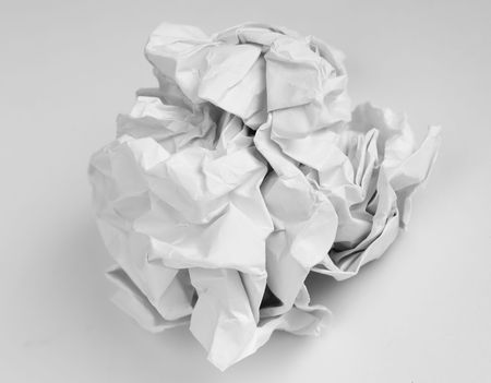 meaningless: crumpled white paper on a grey background