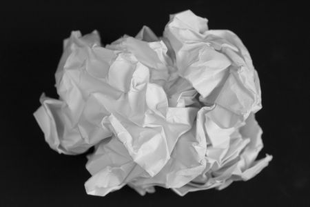 meaningless: crumpled white paper on a black background