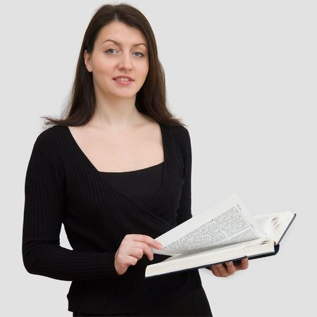 educating: beautiful woman with big Bible on a grey background Stock Photo