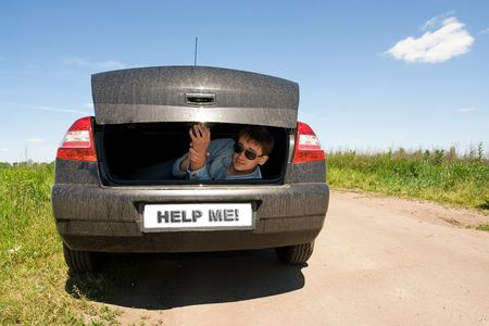 help me: Help me! Man in the car luggage carrier. Stock Photo
