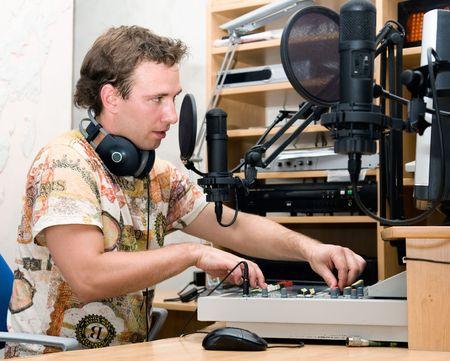 disc jockey: Radio DJ.  Young man with microphone and big headphone.