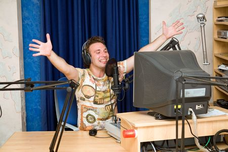 Radio DJ.  Smiling young man with microphone and big headphone. Stock Photo