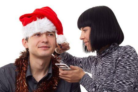 Christmas time. Young man wearing Santa hat. Makeup. photo
