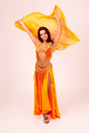 Belly dancer. Attractive girl dances east dance. Orange dress. Stock Photo - 4264840