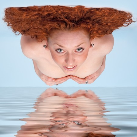 Attractive red-haired woman over blue water photo