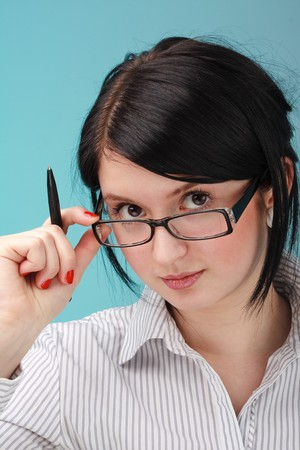 Attractive young woman with glasses and pen on a blue background