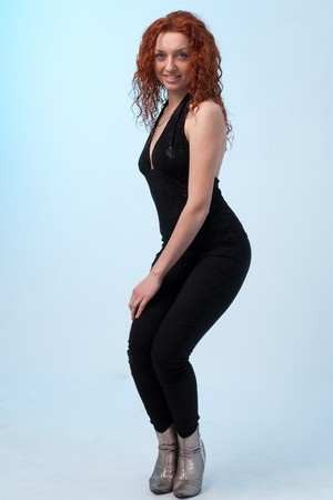 red haired woman: Smiling red haired woman standing against blue background