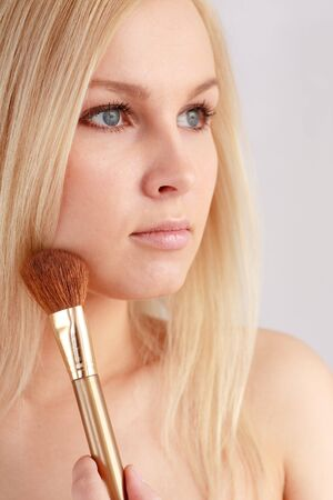 Beautiful young woman with make up brush Stock Photo - 4542882