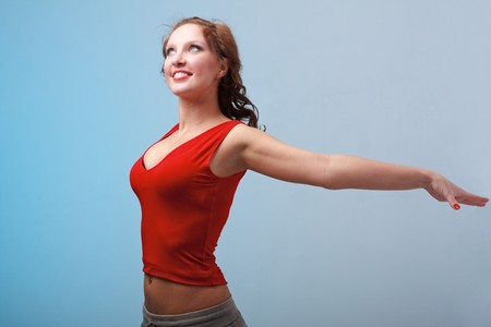 Attractive young sportswoman exercising against blue background Stock Photo - 4542901