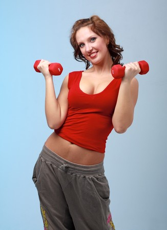 Attractive young woman exercising with dumbbells against blue background Stock Photo - 4542910