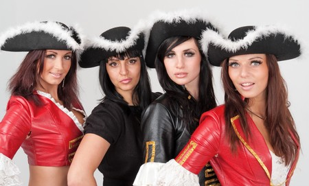 young women in pirate costumes on a gray background photo