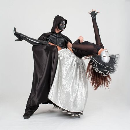 Young dancers in costumes and masks on a gray background photo