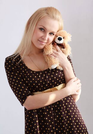 Attractive girl with toy bear  standing against gray background photo