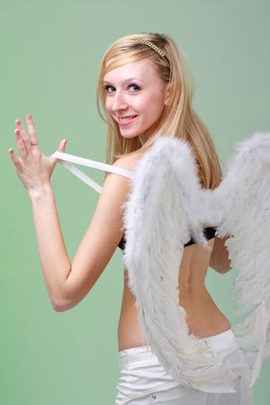 Beautiful young woman with white angel wings on a green background. photo