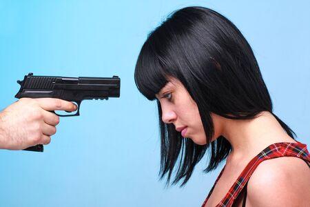 Innocent victim. Young beautiful woman and gun. photo