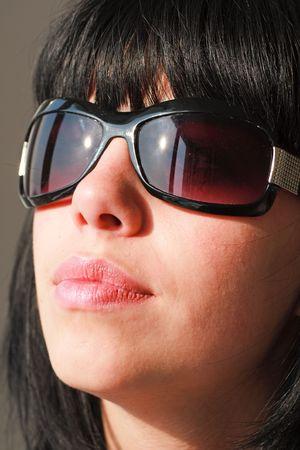 Eyewear. Young woman wearing sunglasses close up. photo