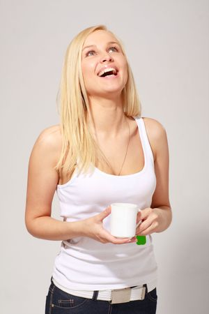 Smiling young woman with white tea cup photo