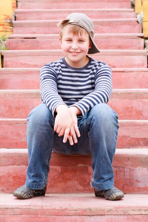 joyful little boy sitting on stairs in the park Stock Photo - 4956221