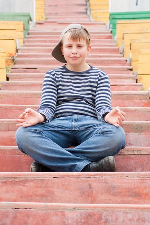 meditating boy sitting on stairs in the park photo