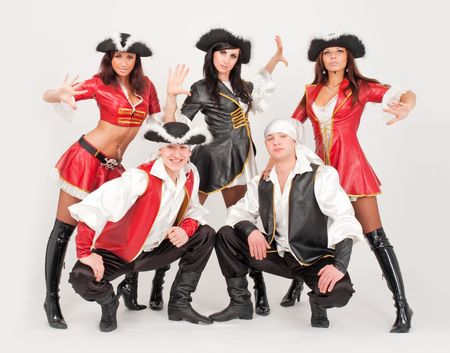 Young dancers in pirate costumes standing against isolated gray background photo