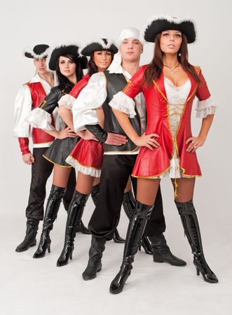 dancers in pirate costumes standing on a gray background photo