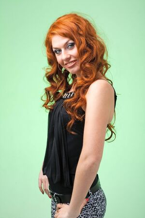 Attractive red haired woman on a green background photo