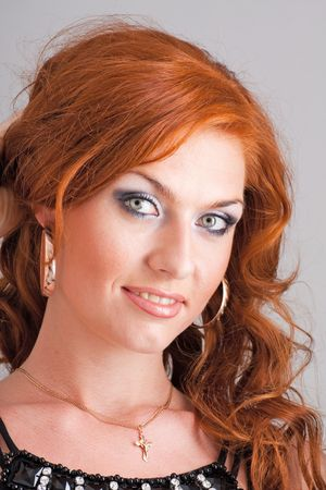 Beautiful red haired woman on a gray background
