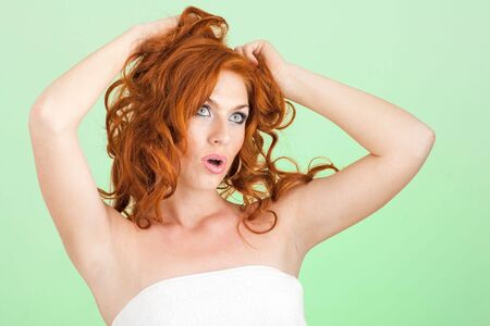 Surprised girl. Beautiful red haired woman on a green background. photo