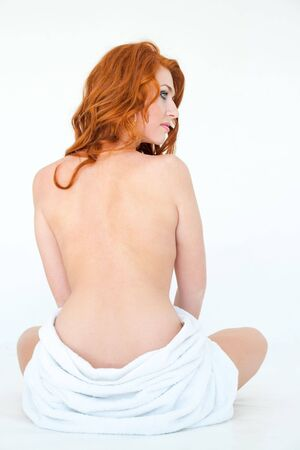 beautiful young woman with towel sitting on a white background photo