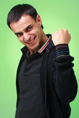 Yes. Happy young man on a green background. Foto de archivo