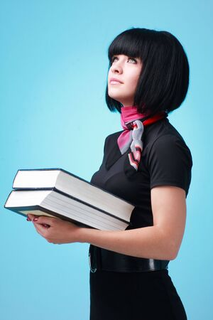 Student with big books on a blue background photo