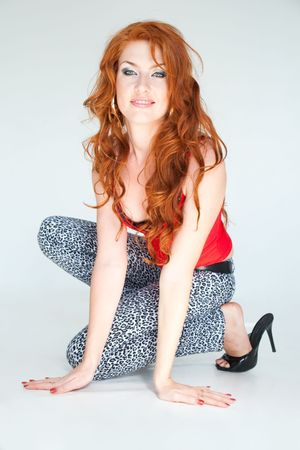red haired woman: young red haired woman sitting on a gray background Stock Photo
