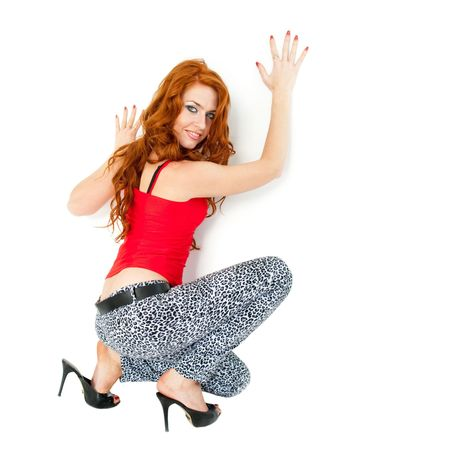 red haired woman: Attractive red haired woman sitting on a white background
