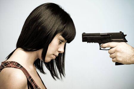 kill: Innocent victim. Young beautiful woman and gun.  Stock Photo