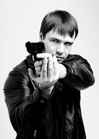 Aiming. Serious man with a gun close up  photo