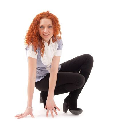 red haired woman: young red haired woman sitting on a white background